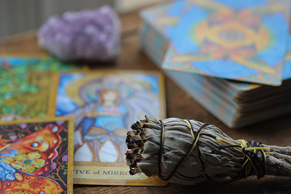 a table strewn with tarot cards and a sage smudger