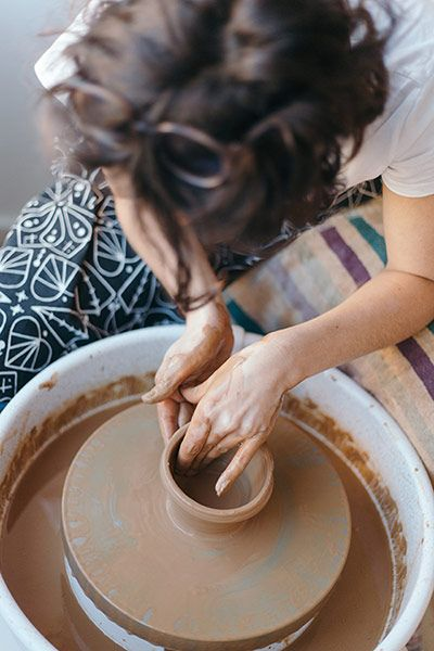 A ceramics artist works on shaping a vessel at her pottery wheel