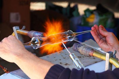 closeup of hands holding a piece of glass being fired